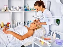 Eyebrow treatment of woman middle-aged in spa salon. Eyebrow treatment of women middle-aged in spa salon. Tweezing eyebrow by beautician. 40s old female under stock image