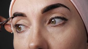 Eyebrows care. Attractive woman cuting with scissors excess hair of eyebrows. Close-up. stock footage