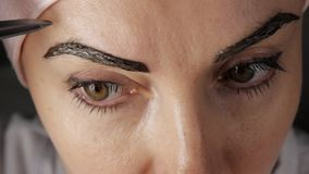 Eyebrows care. Attractive woman getting her eyebrows threaded. Close-up. stock footage