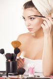 Eyebrows combing. Girl with towel on head combing her eyebrows with a Eye brow brush Royalty Free Stock Image