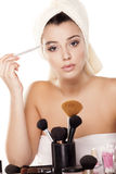Eyebrows combing. Girl with towel on head combing her eyebrows with a Eye brow brush royalty free stock photo