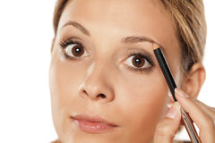 Eyebrows shaping. Young beautiful woman shaping her eyebrows with a pencil for eyebrows Royalty Free Stock Images