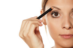 Eyebrows shaping. Young beautiful woman shaping her eyebrows with a pencil for eyebrows Stock Images