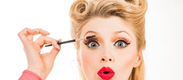 Eyebrows with tweezers close up. Eyebrows Care. Closeup of Woman Beautiful Eye, Long Eyelashes with Professional Makeup