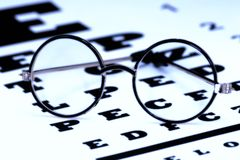 Eyecare. Eyeglasses on a Eyechart Stock Images