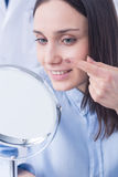 Eyecare is easy with my CL!. Happy woman putting on contact lens, sitting in front of a mirror Stock Photos