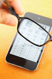 Eyechart en la pantalla móvil con gafas Fotos de archivo libres de regalías