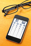 Eyechart on mobile with glasses Royalty Free Stock Image
