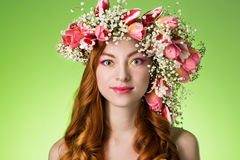 Eyed redhead girl with bright makeup and a wreath of spring flow Royalty Free Stock Photos
