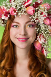 Eyed redhead girl with bright makeup and a wreath of spring flow Stock Photos