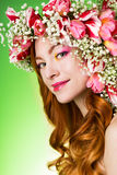 Eyed redhead girl with bright makeup and a wreath of spring flow Stock Image