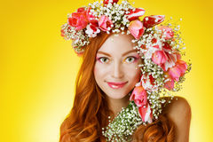 Eyed redhead girl with bright makeup and a wreath of spring flow Royalty Free Stock Images