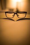 Eyeglass на тени книги светом Стоковое Изображение