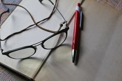 Eyeglass with book and pen Royalty Free Stock Photos