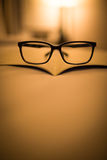 Eyeglass on the book shade by light Stock Image