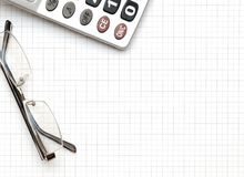 Eyeglass, and calculator on the working paper Stock Photos