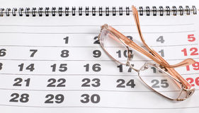 Eyeglass on calendar to schedule plans Stock Photo