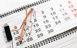Eyeglass on calendar to schedule plans Stock Images