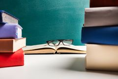 Eyeglass dalej Nakrywa Otwartą książkę z stertami książka obrazy stock