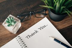 Eyeglass, green plant and notebook with word THANK YOU royalty free stock photography