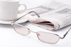 Eyeglass and newspaper Stock Images