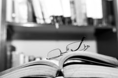 Eyeglass on opened book pages, bookshelf on the blurried background, space for text. Focus on the eyeglass in black and white stock photo