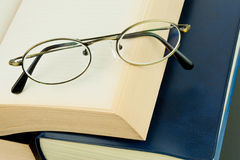 Eyeglass on pile of books Royalty Free Stock Image