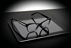 Optical glass on tablet and table. Eyeglass and tablet black technology Stock Photography