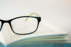 Eyeglasses ανάγνωσης με το ανοιγμένο βιβλίο Στοκ Φωτογραφία