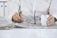 Eyeglasses εφημερίδων και εκμετάλλευσης ανάγνωσης ατόμων Στοκ φωτογραφίες με δικαίωμα ελεύθερης χρήσης