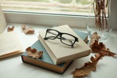 Eyeglasses και ανοικτό βιβλίο με τον ξύλινο πίνακα φθινοπώρου leaveson Έννοια διάθεσης φθινοπώρου Στοκ εικόνες με δικαίωμα ελεύθερης χρήσης