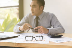 eyeglasses και υπολογιστής στο γραφείο με τον επιχειρηματία που αναλύει το ύφασμα Στοκ εικόνα με δικαίωμα ελεύθερης χρήσης