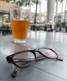 Eyeglasses σε έναν πίνακα και ένα υπόβαθρο είναι ποτήρι της μπύρας Στοκ φωτογραφία με δικαίωμα ελεύθερης χρήσης