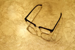 Eyeglasses σε έναν χρυσό πίνακα Στοκ φωτογραφία με δικαίωμα ελεύθερης χρήσης