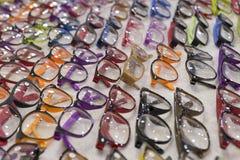 Eyeglasses σε πολλά διαφορετικά χρώματα ανάμεικτα στην έκπτωση on-line Στοκ Φωτογραφία