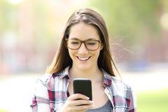 Eyeglasses девушки нося проверяя мобильный телефон Стоковое Изображение