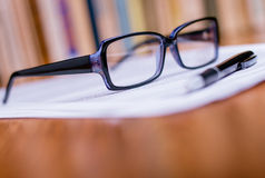 Eyeglasses и ручка na górze белой бумаги Стоковое Изображение