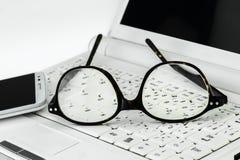 Eyeglasses и сотовый телефон на малой компьтер-книжке Стоковое Фото