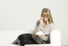 eyeglasses книги читая женщину софы Стоковые Фото