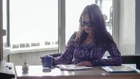 Eyeglasses коммерсантки брюнет нося работая на портативном компьютере Стоковое Изображение