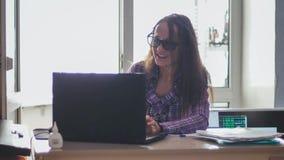 Eyeglasses коммерсантки нося работая на портативном компьютере Стоковая Фотография RF