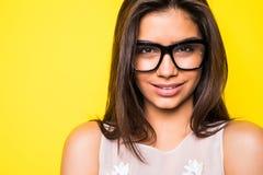Eyeglasses маленькой девочки нося в желтой предпосылке смотреть девушки камеры Стоковые Изображения RF