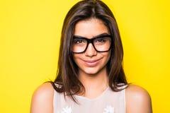 Eyeglasses маленькой девочки нося в желтой предпосылке смотреть девушки камеры Стоковые Изображения