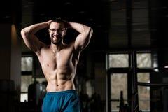 Eyeglasses молодого культуриста нося изгибая мышцы стоковые изображения rf