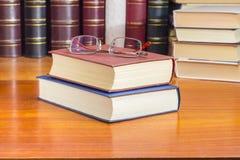 Eyeglasses на 2 закрытых книгах против других книг Стоковое Изображение