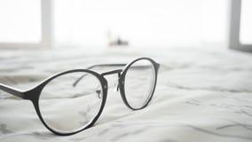Eyeglasses на кровати Стоковая Фотография