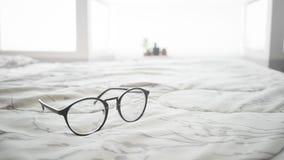 Eyeglasses на кровати Стоковые Изображения RF