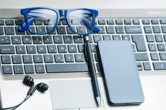 Eyeglasses на клавиатуре компьтер-книжки с smartphone, концепция офиса карандаша и наушников Стоковое Изображение