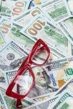 Eyeglasses на предпосылке денег доллара предпосылки Стоковые Изображения RF