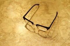 Eyeglasses на таблице золота Стоковая Фотография RF